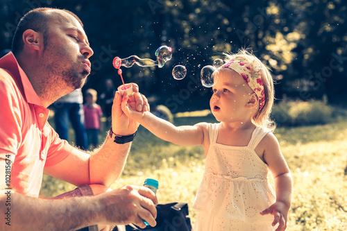 Fotografía  Papá y burbujas soplando hija