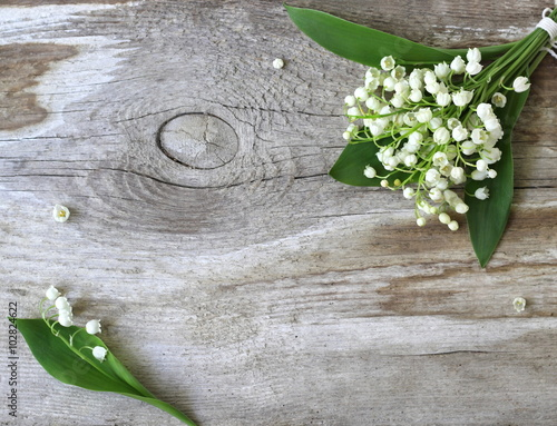 Wall Murals Lily of the valley Decorative border or frame with lily of the valley flowers on a wooden background. Photo from above.