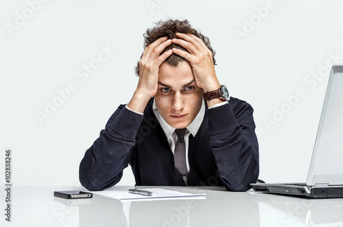 Valokuva  Entrepreneur dissatisfied with his earnings, profit, income, gain, benefit, margin / modern businessman at the workplace working with computer on grey background