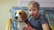 9 years old kid and 5 month old beagle puppy sitting on sofa. Portrait of child and his cute pet dog in home interior. Funny couple of two sitting together.