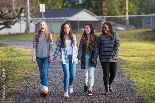 Obraz Group of young girls holding hands and laughing while walking on - fototapety do salonu