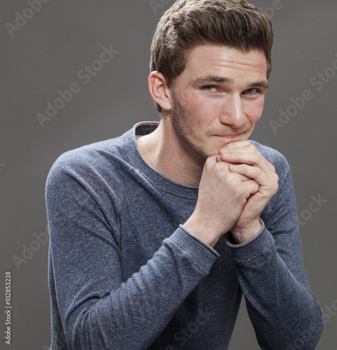Fotografie, Obraz  seduction concept - portrait of a smiling seductive young male student with cheeks blushing leaning his face on hands, gray background