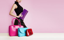 Woman With A  Purse Passing In Front Of The Colorful Bags. Fashion Image With Copy Space.