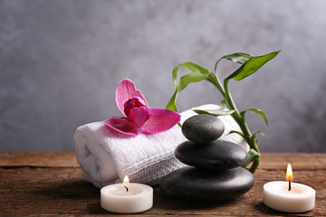 Obraz na płótnie Canvas Spa stones with candles, purple orchid, bamboo and towel on wooden table against grey background