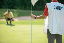Golf Caddy Holding A Flag For Putting, Golfer In The Background Reading Green
