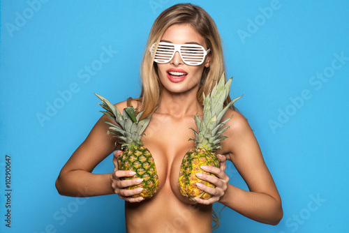 Fotografía  Young sexy woman happy smiling only in glasses posing on blue background with pi