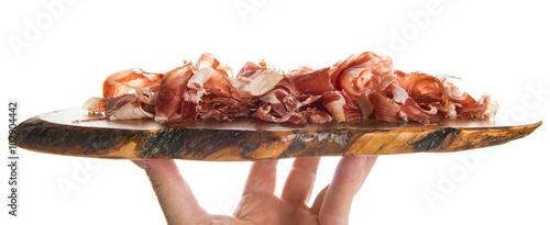 Foto  Tabla de olivo con jamón serrano cortado a cuchillo en virutas aislado sobre fon