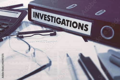 Fotografía  Ring Binder with inscription Investigations on Background of Working Table with Office Supplies, Glasses, Reports
