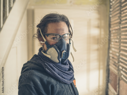 Woman with dust mask and goggles in hallway - Buy this stock photo