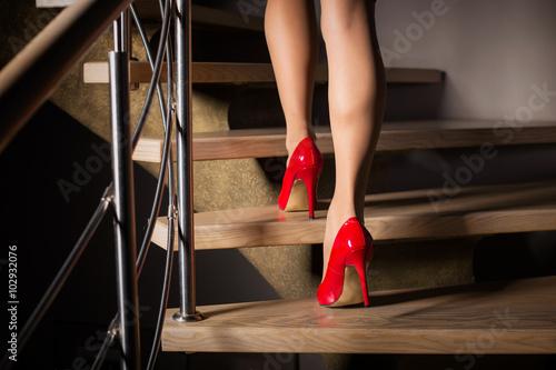 Fotomural Woman in red high heels walking upstairs