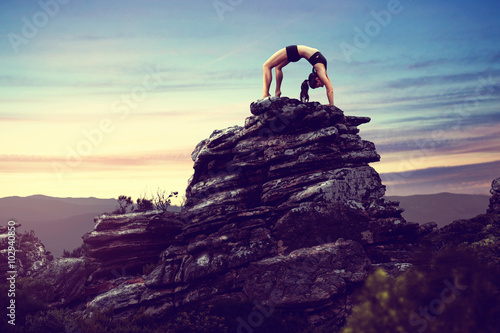 Foto  Woman does gymnastics on a rock