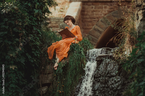 Fotografie, Obraz  The beautiful countess in a long orange dress sits near a source of water and re