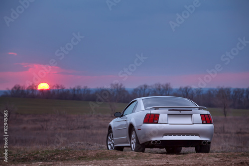 фотография  Car stay on dirt road at sunset