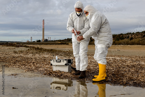 Valokuva  Experts Analysis Water / Two technicians levying of water samples from the river to perform the analyzes