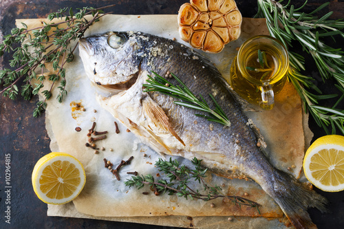 Photo  Grilled fish sea bream with aromatic spices, herbs and lemon
