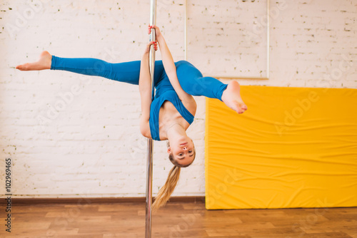 Fotografie, Obraz  girl in a blue dress in the gym on a pole splits, exercise on a pole