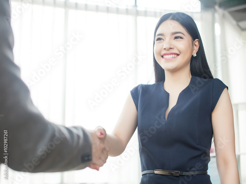 Fotografia  Smart and confident Asian businesswoman smiling and shaking hand