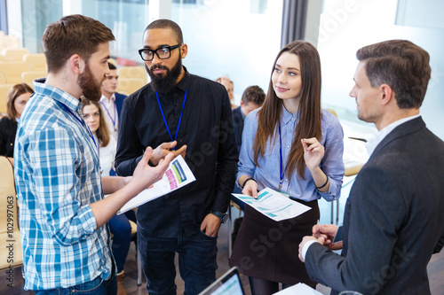 Fotografía  Confident business people standing and discussing financial report in office