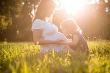 Child Kissing Belly Og Pregnant Mother