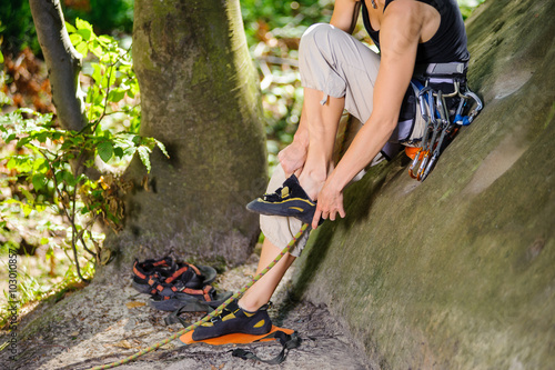 In de dag Alpinisme Female climber sitting on a big rock and putting her climbing shoes on. Getting ready for climb. Climbing equipment. Outdoor summer day.