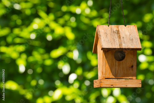 Photo Old wooden birdhouse hanging with ropes