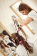 Female hairdresser drying woman's hair