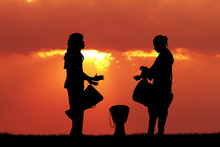 African Men Playing The Drum At Sunset