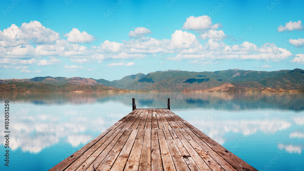 Fototapety, obrazy: Perspective view of a wooden pier in a completely calm lake with reflections of the sky