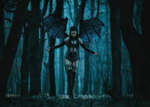 Girl Vampire Demon With Bat Wings, Woman Fantasy Succubus Walks In Dark Forest. Lady In Dark Gothic Leather Latex  Black Sexy Costume, Dress. Huge Wings And Sexy Outfit, Fashionable Art Colors.