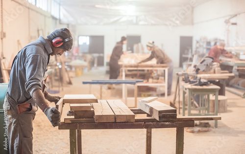 Man doing woodwork in carpentry / Carpenter work on wood plank in workshop