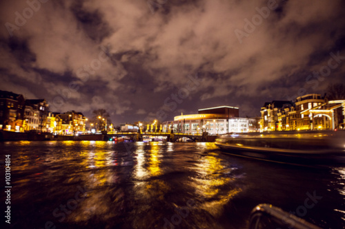 Photo Stands Paris Night lighting reflections in Amsterdam channels from moving cruise boat. Blurred abstract photo as background.