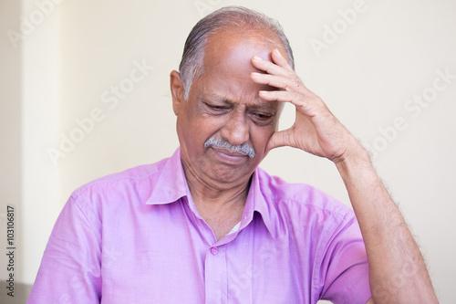 Closeup portrait, morose elderly pensioner, downcast gloomy, resting hand on hea Canvas Print