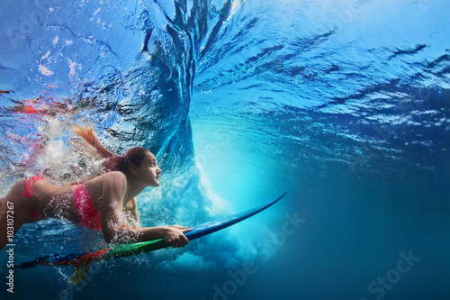 Young girl in bikini - surfer with surf board dive underwater under big ocean wave Family lifestyle, people water sport adventure camp and beach extreme swimming activity on summer vacation with child