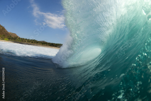 Wall Murals Ocean a powerful wave breaking on a white sand beach in Indonesia