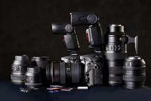 DSLR Camera, Lens And Flash Cards On Black