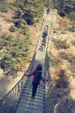 Trekkers Crossing A Suspension...