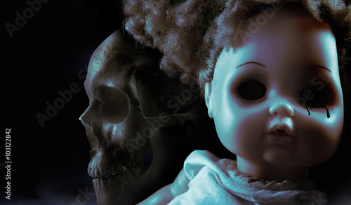 Photographie  Scary horror plastic doll face with black tears and human skull on background