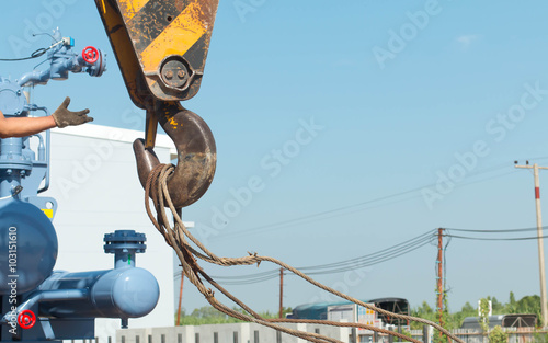 Industrial Crane operating lifting against sunlight and blue sky Canvas Print