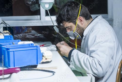 Valokuva  dental technician using dental burs with zirconium teeth.
