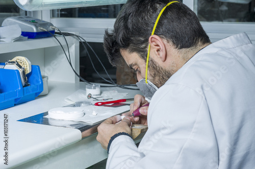 Fényképezés dental technician using dental burs with zirconium teeth.
