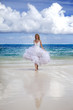 beautiful woman in a wedding dress runs on waves of the sea