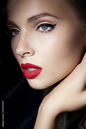 Fotografie, Obraz  Krásná dívka s červené rty a černými šipkami na oči