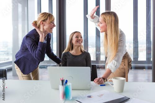 Fotografia  Three business women in modern office celebrating good project results