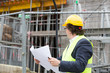 Construction manager with yellow safety jacket and hardhat looking at construction site