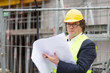Architect with yellow safety jacket and helmet at work