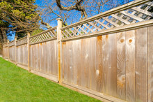 Wooden Fence With Green Lawn A...