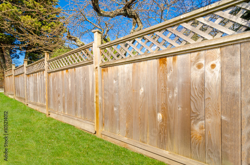 Carta da parati wooden fence with green lawn and trees