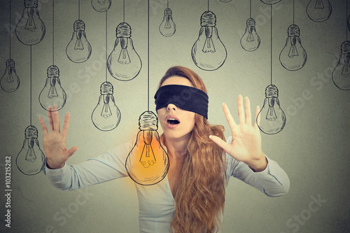 Photo Blindfolded young woman walking through light bulbs searching for bright idea