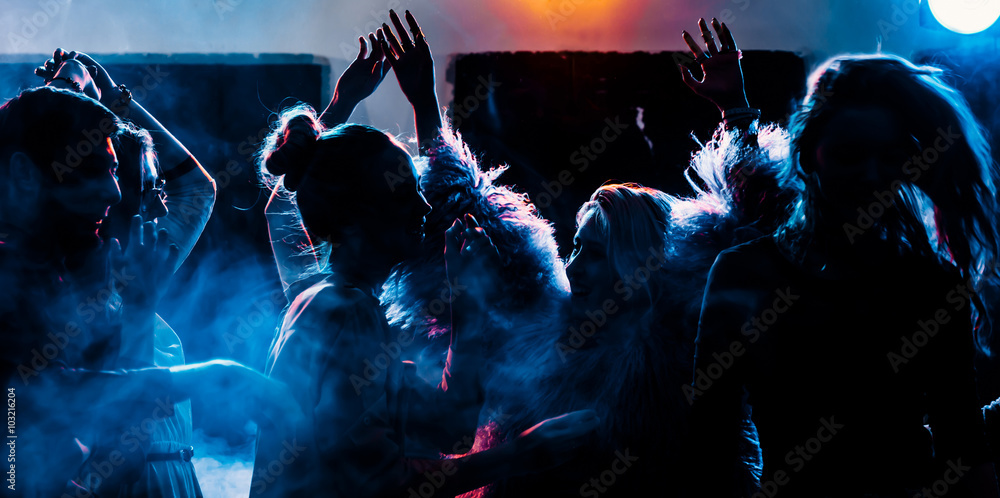 Fototapeta party at a nightclub, young people boys and girls dancing in a smoke