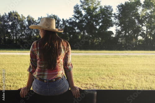 Fotografie, Obraz  Cowgirl lady woman female wearing cowboy hat and flannel shirt with jeans sittin